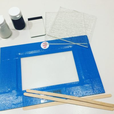 Image of the screen for printing on glass with, squeegee and enamels in black and white