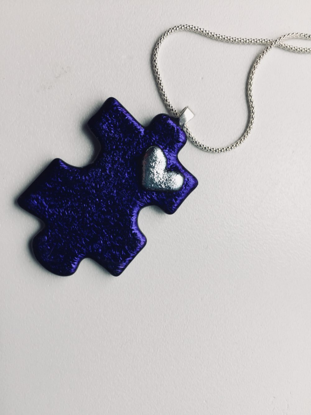 Purple puzzle piece in glass wiht silver heart detail