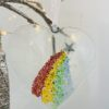 Fused glass heart hanger with rainbow decoration and copper star decoration and white trail detial.